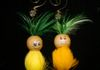3 inch feathered covered pineapple ornament with hand painted faces