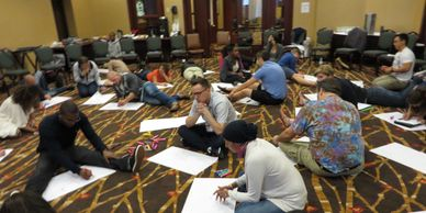 SJTI participants sitting on the floor doing an activity with newsprint paper.