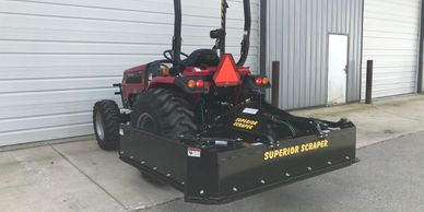 Folding manure scraper on tractor for easy maneuverability