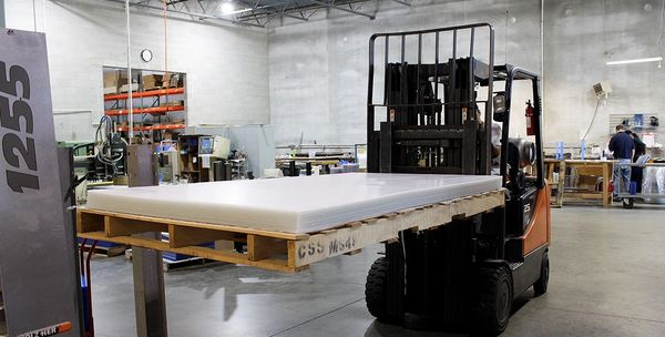 Fork lift carrying full size acrylic sheets to the large format cutter.
