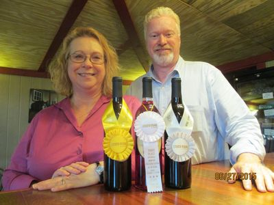 A picture of the owners of Chateau MerrillAnne, Emily and Kenny, posing with award winning wine.
