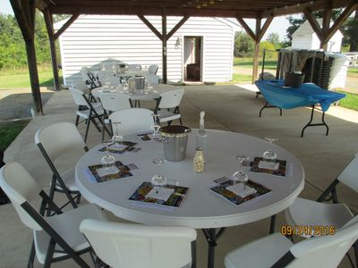 Picture of multiple large tables set up for a wine tasting.