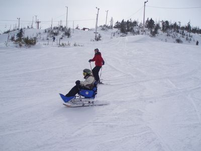 Skier sitting in a bi-ski tethered by an instructor.