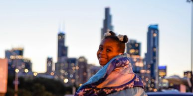 A little girl sitting on top of a car at a CHI-Together event.