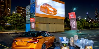 A 2021 Nissan Sentra parked in front of a movie screen at CHI-Together's Drive-In Date Night event.