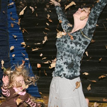 Woman and child laughing and throwing autumn leaves into the air.