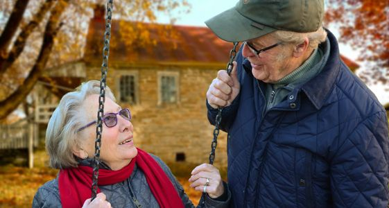 elderly woman talking to elderly man while on swing set