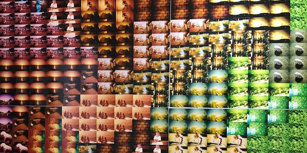 Wall of pink, brown and green photographs arranged in a pattern. Photograph taken in Japan.