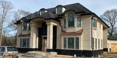 Big beige brick house with black trim under construction