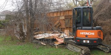 Excavator demolishing derelict garage