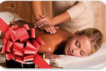 woman relaxing on massage table getting massage.  Big red bow and candles in the forefront.