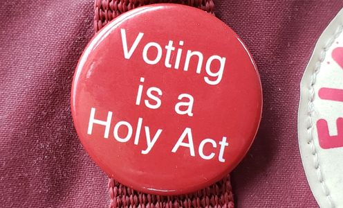 "Round, red button reading ""Voting is a Holy Act"" pinned to a backpack."