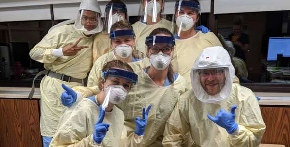8 health care workers pose in PPE gear: yellow gowns, blue gloves, face shields and white masks.