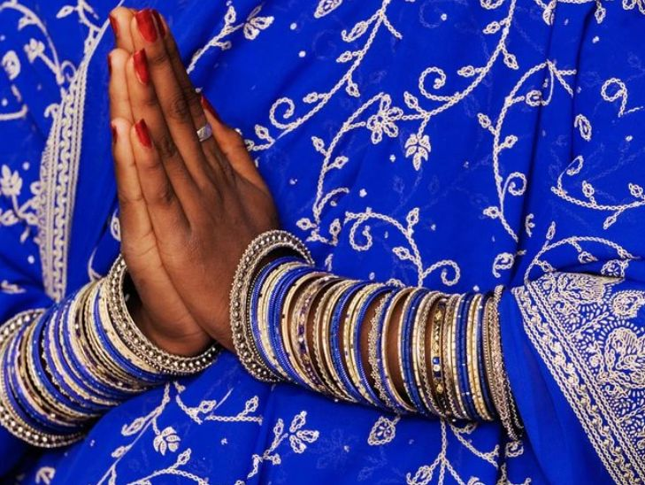 Woman in beautiful blue sari in Namaste pose.