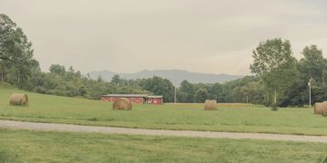 Old red tractor barn in front of peacful Peachtree Mountain. Heather Fink Photography