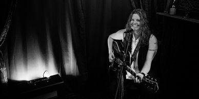 Kristine Jackson Christine Jackson MusicByKJ Live performance photo in black and white. Kristine is smiling an playing an electric guitar on an intimate stage