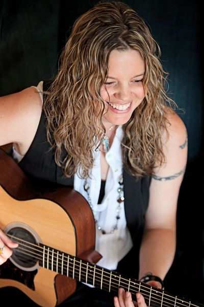 Kristine Jackson Christine Jackson MusicByKJ Head-shot with top of acoustic guitar visible and Kristine smiling