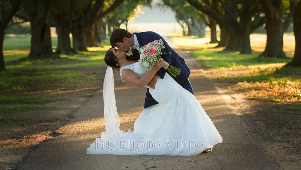 Wedding Couple kissing down a tree lined road