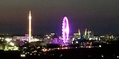400 foot tall glowing purple Ferris wheel and drop tower glowing white at Icon, Orlando at night.