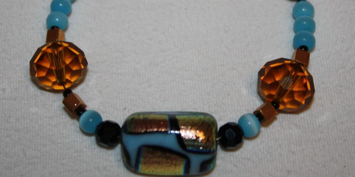 Beautiful glass blue, gold and black foil handmade jewelry bead brought to life with gold plated bea