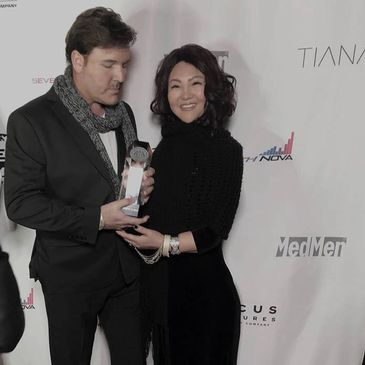 Steven Vitali and Grace Yang Vitali holding his HMMA Award for Best Instrumental 2018. Red Carpet.