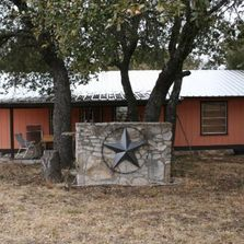 Ranch house with metal star hanging on back of BBQ pit.