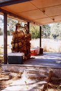 View of porch with wood stack and coolers.