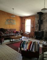 View of living area with couch, coffee table, wood stove heater, and chairs.