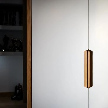 Contemporary fitted wardrobes with oak handle inserts.
