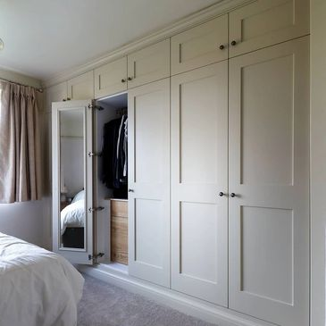Wall of Shaker Wardrobes with internal oak drawers and mirrored doors