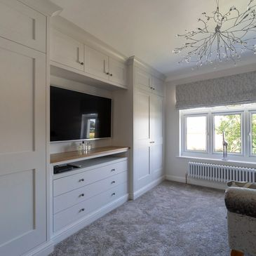 Fitted Shaker wardrobes with space for TV. Spray finished in Farrow and Ball 'ammonite'