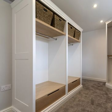 Oak and white fitted dressing room wardrobes with oak drawers and wicker basket storage.