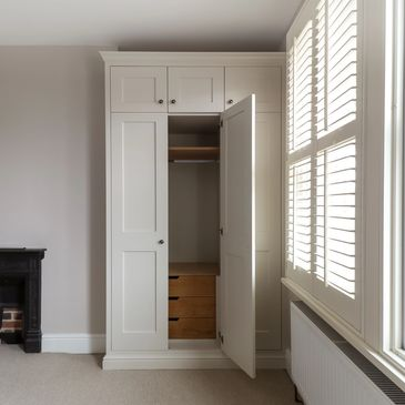 Alcove shaker wardrobes with oak internal drawers. Spray finished in Farrow & Ball 'Skimming Stone'