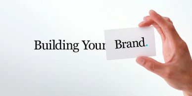 "Words  ""Building Your Brand"" A hand holds a card with the word ""Brand."" to Podcasts builds brands."