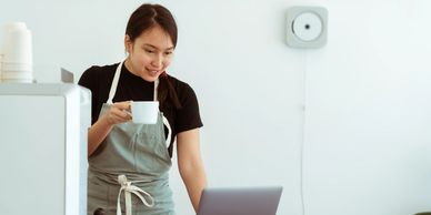 Girl in the kitchen with coffee and laptop