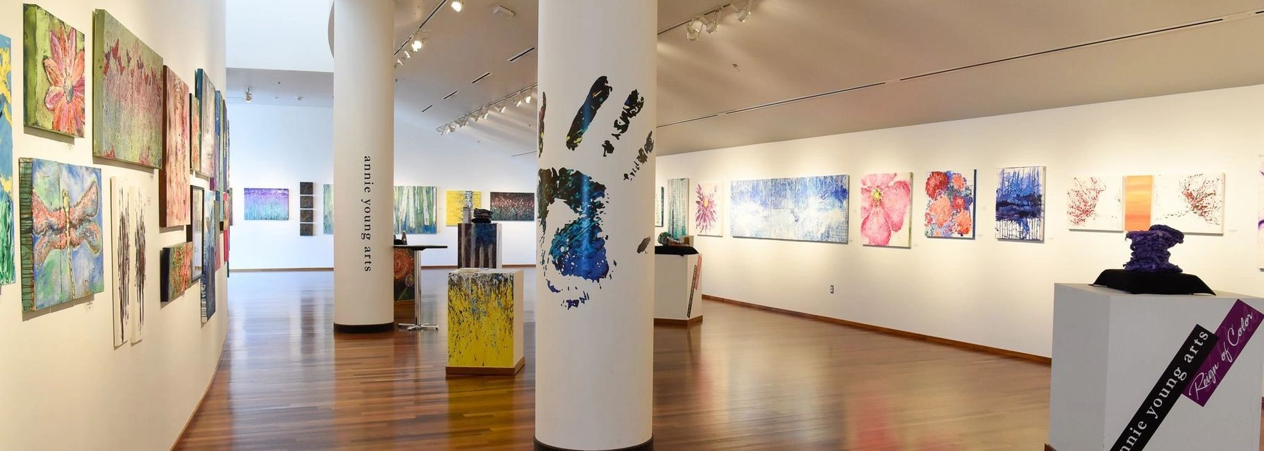 art gallery displaying a colorful array of annie's artwork. painted hand print wraps pillar