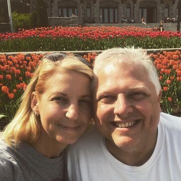 couple posing for picture in front of flowers