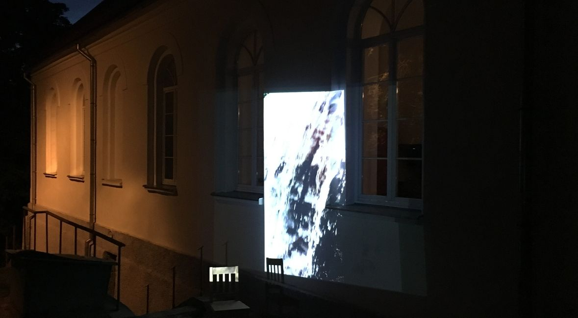 Projected image of water on exterior of former synagogue, at night.