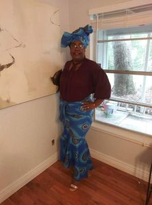 Customer wears mermaid skirt and matching head wrap in African wax print by Alagema Fabrics & Accessories.