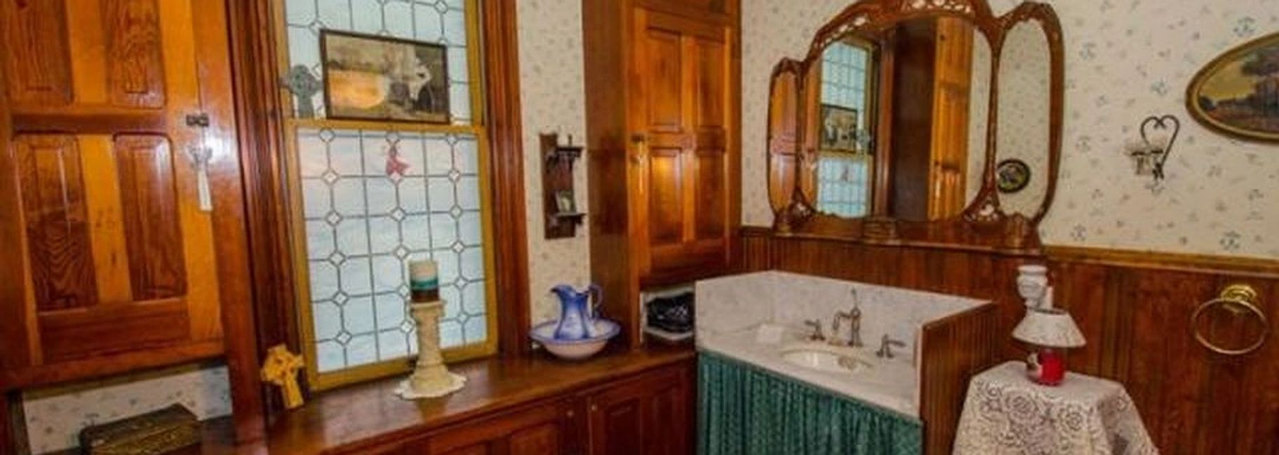 Wooden cabinets surrounding an old marble sink in a half bathroom.