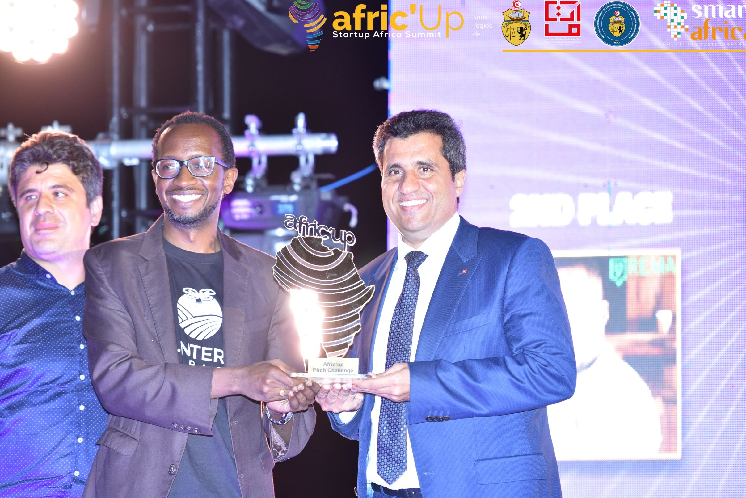 Lentera Africa Co-founder and CEO Moses Kimani (Center) receives the Afric'up trophy from  H.E. Anou