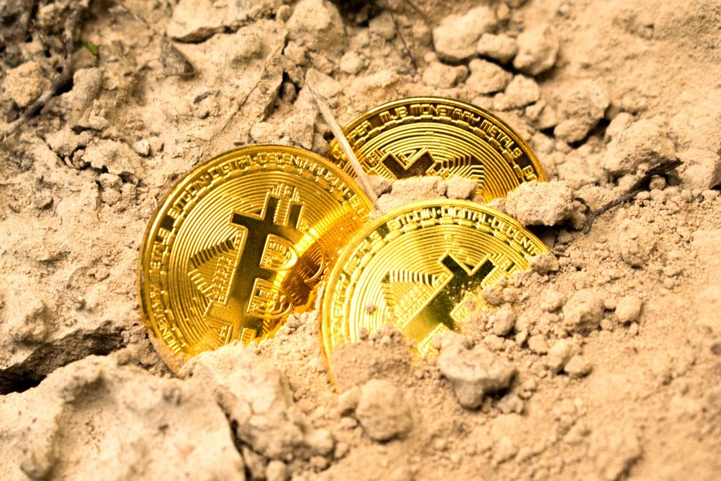 Bitcoin Novelty coins buried in the sand