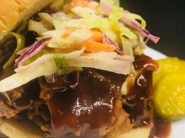 BBQ'ed pulled Jackfruit with cole slaw. RayJay's BBQ sauce and a zesty bread and butter pickle.