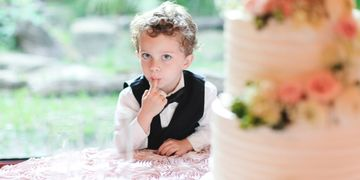Little ring bearer puts finger in wedding cake