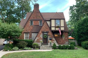 Red Brick and Beige Two Story Tudor House On Sunny Day