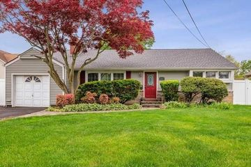 One Story Beige Vinyl Ranch Home With Big Red Tree On Sunny Day