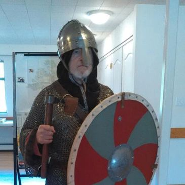 Viking man in chainmail armor with shield and axe.