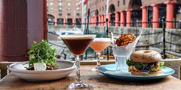A selection of our food & drinks on a table with a view of the Albert Dock