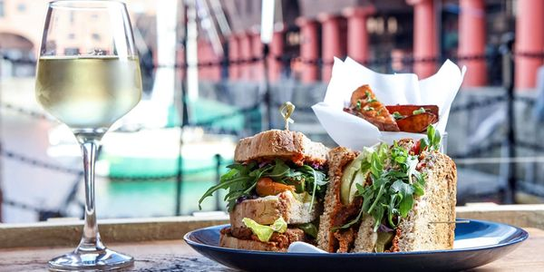 Vegan Club Sandwich with a Large glass of Pinot Grigio on a table with a view of the Albert Dock