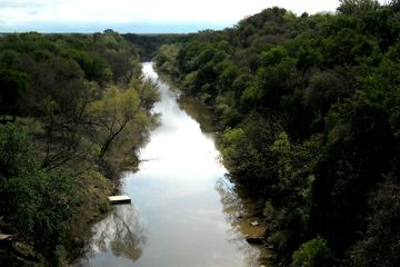 "Photograph of Colorado River in San Saba and Mills County, Texas from the Rengency Bridge. It is one of the last suspension bridges in Texas. Fondly named the ""Swinging Bridge"" locally, it over looks the area of the river where several musicians and song writers often meet up for old-school,  backwoods acoustic concerts as true as Texans are."
